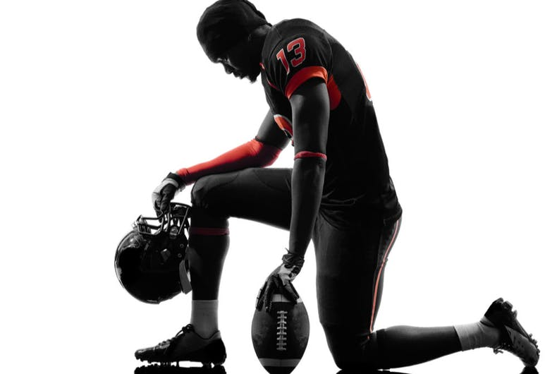 A football player takes a knee before the game