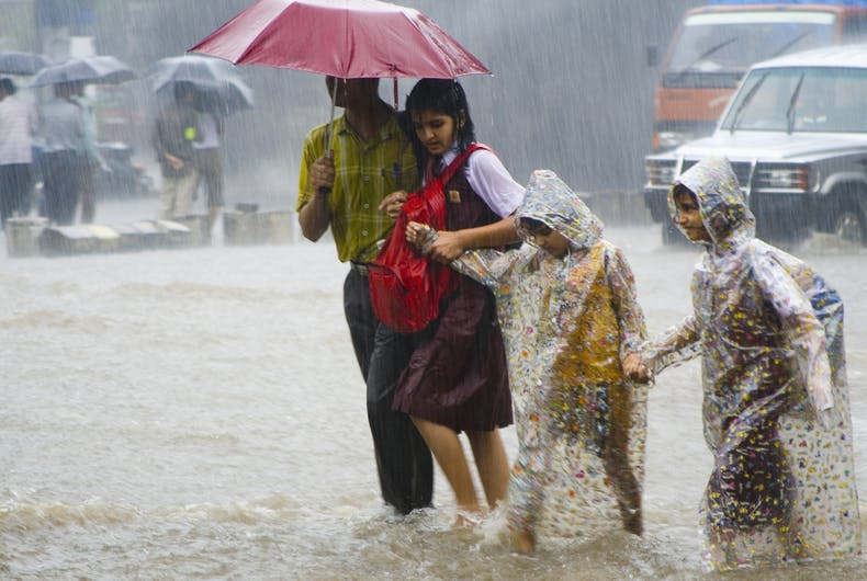 Three children go to school with their parent in monsoon rain in Mumbai, India.