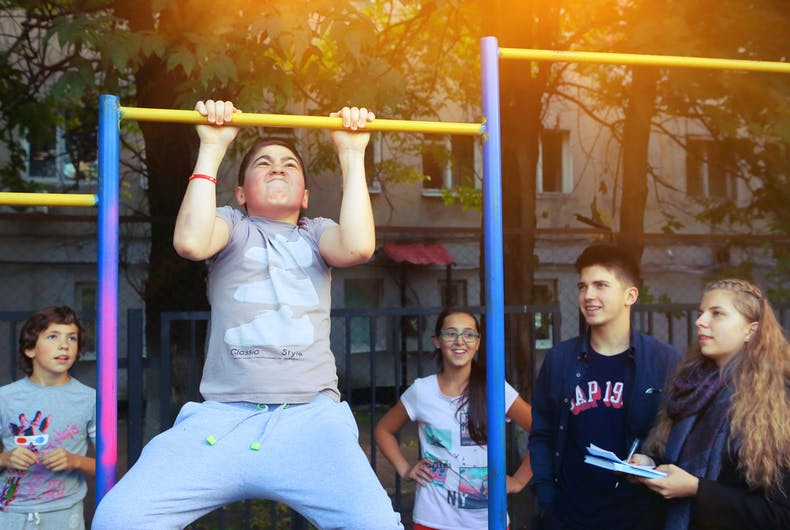 Unidentified school kids on outdoor sport pull up exercises competition in school yard in Moscow