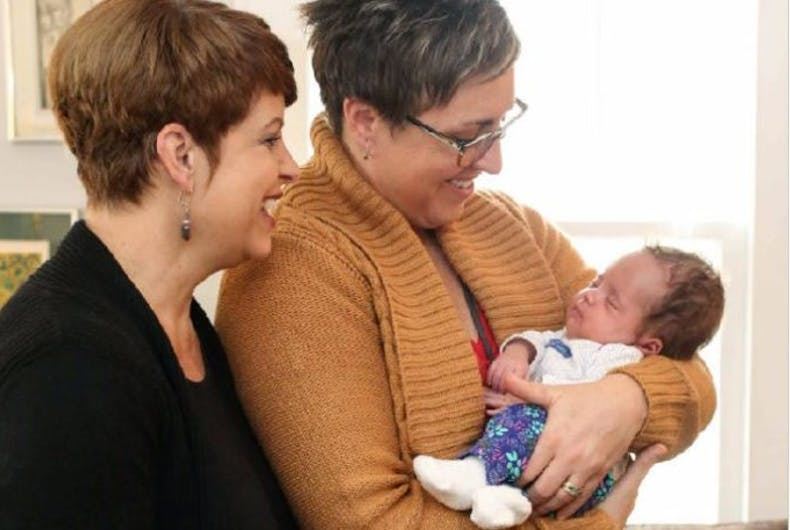 Jackie and Lisa Phillips-Stackman hold their daughter, Lola.