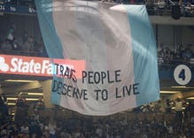 Activists unfurl huge banner supporting trans rights during World Series