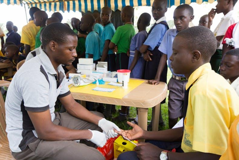 Nkokonjeru, Uganda June 22 2017: A health worker tests a boy for HIV.