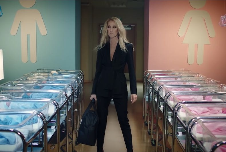 Celine Dion standing in front of babies dressed in pink or blue.