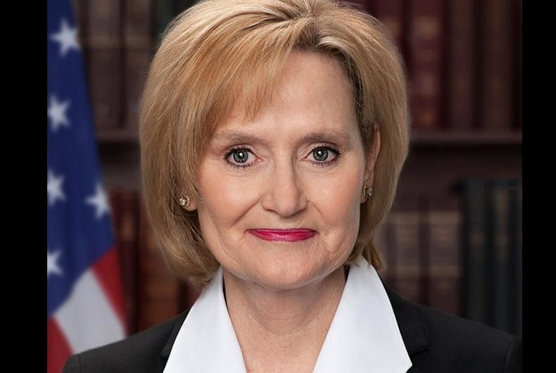 Cindy Hyde-Smith in front of books and an American flag