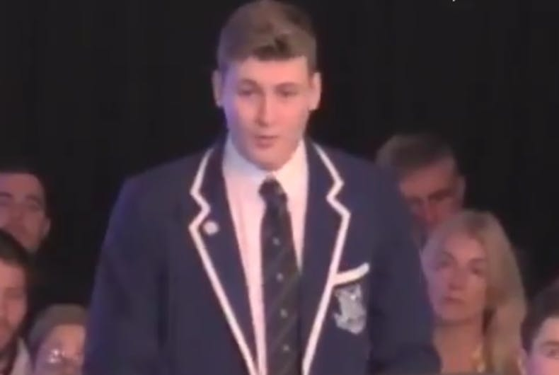 A boy in a blazer at a lectern.