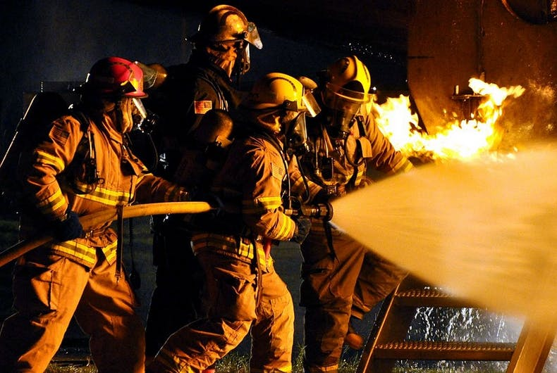 Firefighters holding a hose in a demonstration.
