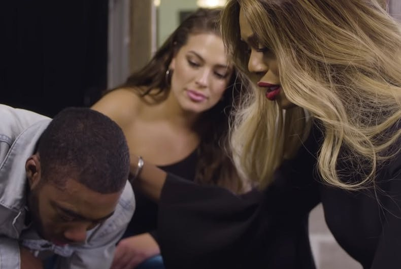 A man crouching with Laverne Cox's hand on his shoulder and a woman in the background