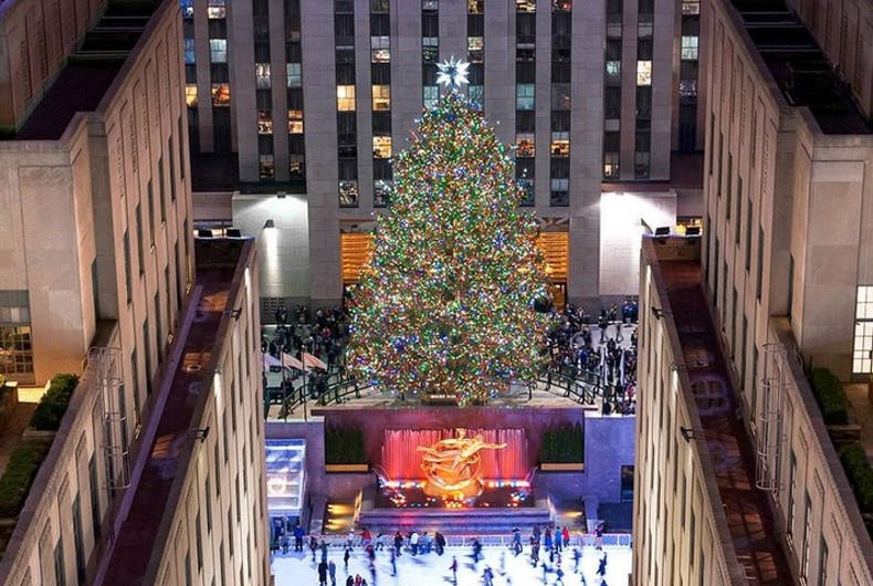 A Christmas tree at the Rockefeller Center flanked by buildings and next to an ice skating rink
