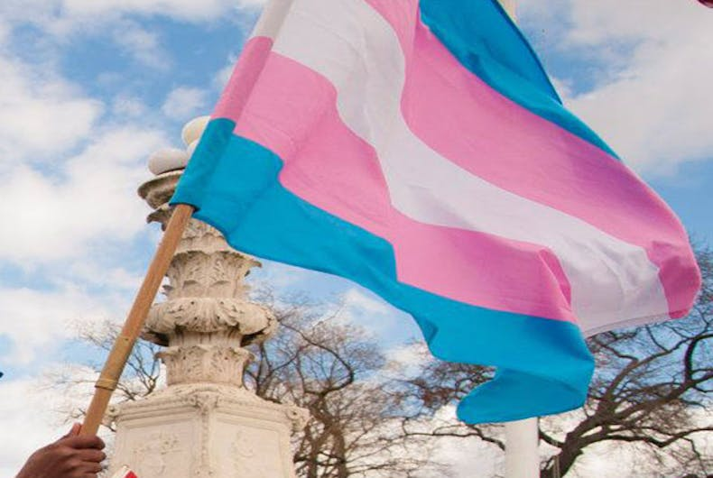 The transgender flag beind waved on a partly cloudy day.