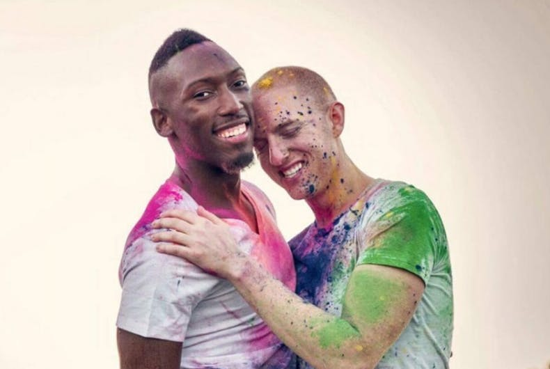 Two men holding each other, covered in colorful paint.