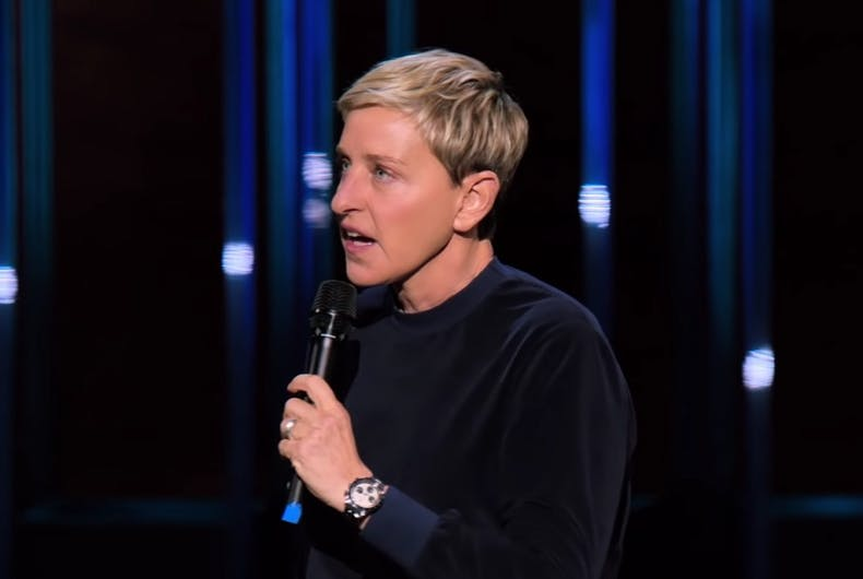 Ellen in a black sweater holding a microphone.