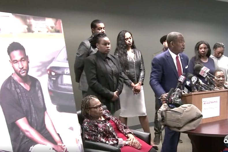 A press conference with a lawyer at a lectern and the family of Jonathan Hart behind him. There is a large image of Jonathan Hart.