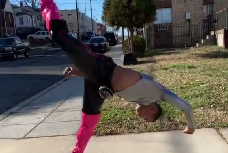 A boy in heels on the sidewalk doing a spinning kick