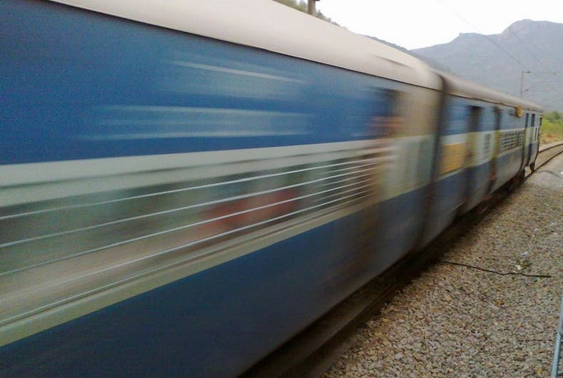 A blue train, moving fast.
