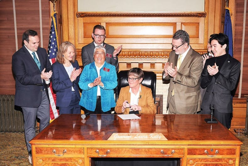 Kansas Governor Laura Kelly (D) signs an executive order restoring employment protections for LGBTQ state employees.