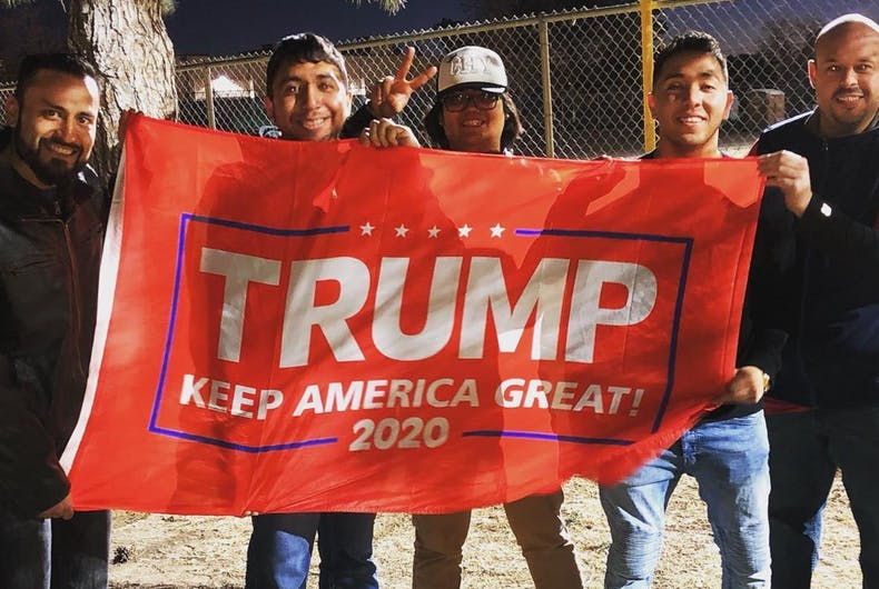 Johnny Alcantar poses with friends behind a banner during a Donald Trump rally in El Paso.
