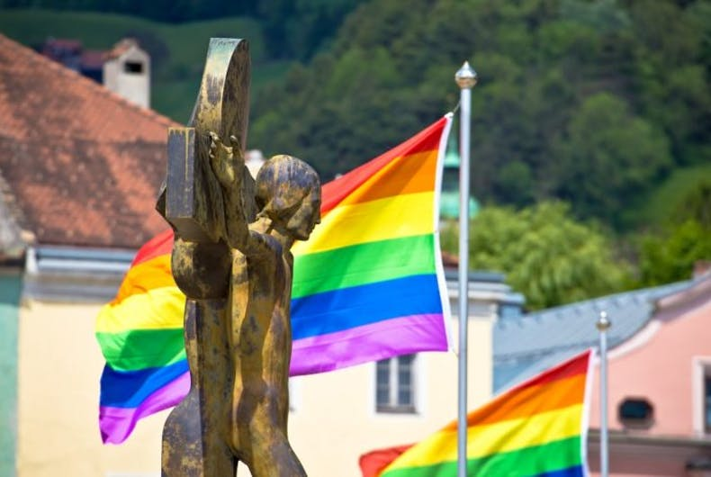A crucifix and rainbow flags in the background
