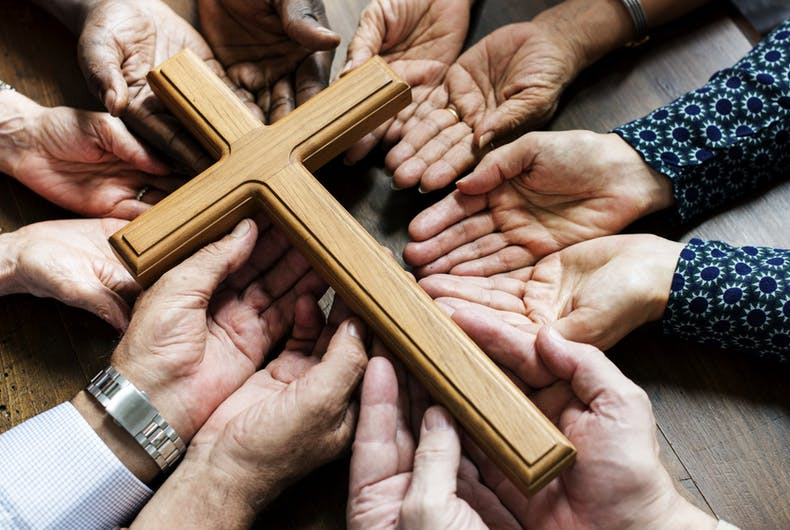 Group of christianity people pray together by using their hands to hold up a medium-sized cross.