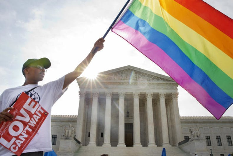 A person holding a rainbow flag in front of the Supreme Court