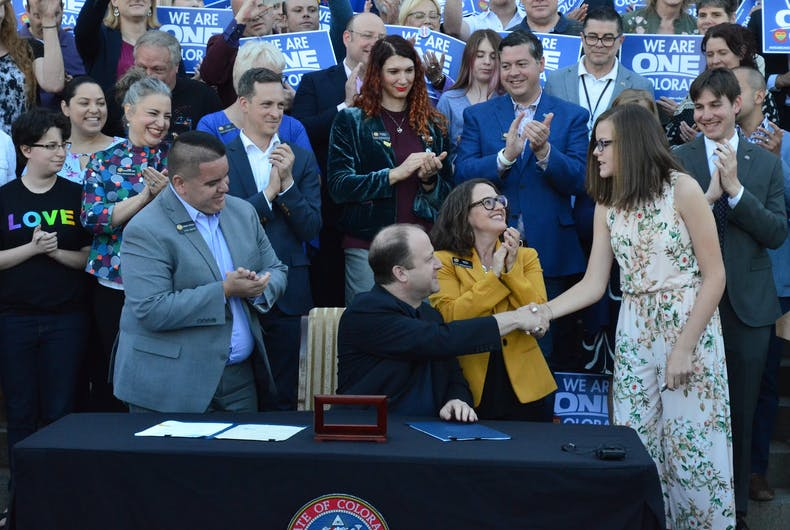 Governor Jared Polis hands the pen he used to sign Jude's Law to the legislation's namesake.