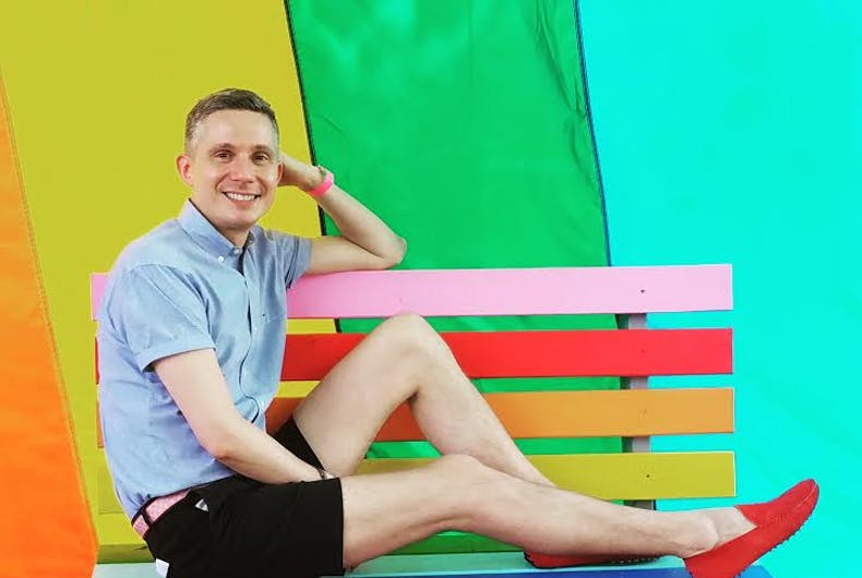 Gay Macy's employee Matt Ossenfort poses in a blue polo and shirts on a rainbow bench, against a rainbow backdrop.