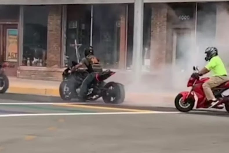 A motorcycle produces a lot of smoke on the rainbow crosswalk