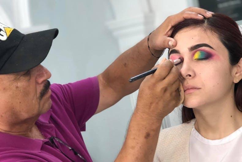 Raúl Santiago applies eye shadow to a model during class