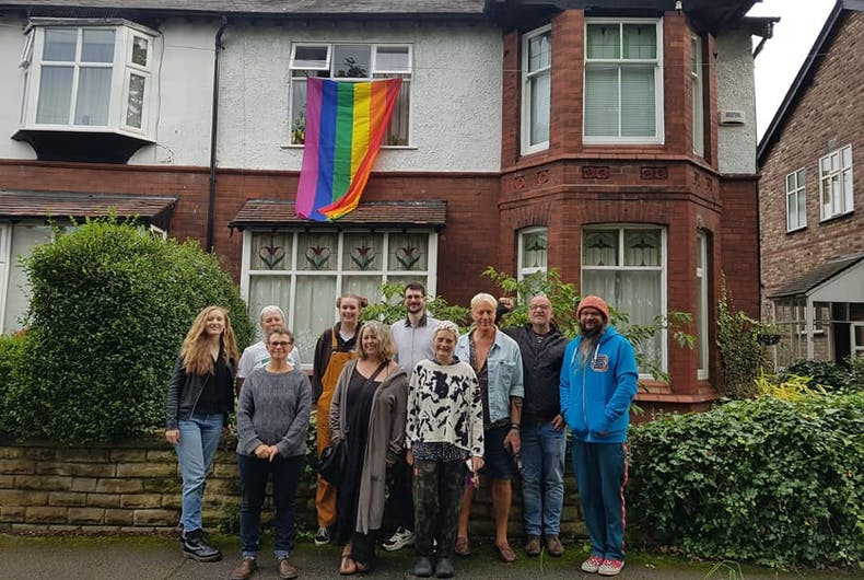 People standing in front of a house with the rainbow flag