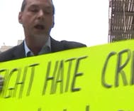 Gay man threatened with his own sign at protest against hate