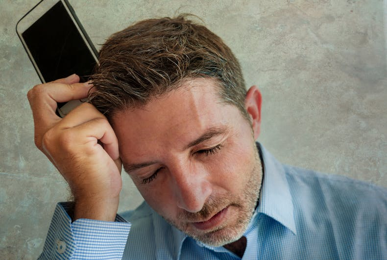 grunge portrait of frustrated and depressed business man holding mobile phone in stress feeling disappointed suffering headache and anxiety looking tired and under work pressure