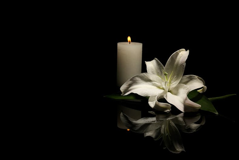 A candle and a lily, representing the concept of mourning