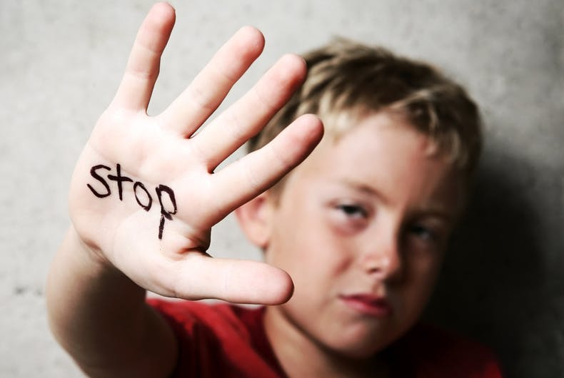 A young blond boy raises his hand, the word 'Stop' is written on it.