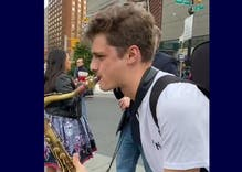 Street preacher's hate speech drowned out by two music students with saxophones
