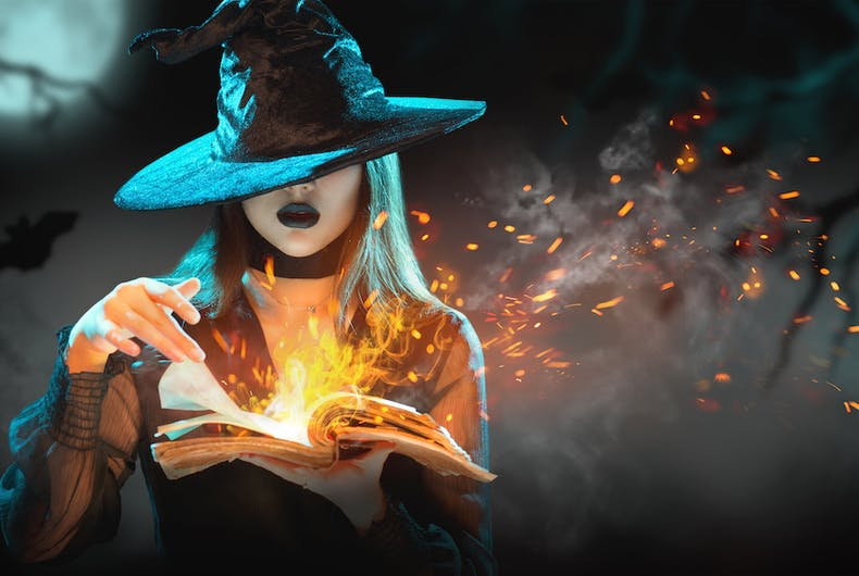 Beautiful young woman in witches hat conjuring, making witchcraft by making flames erupt from the pages of a book of magic during a full moon..