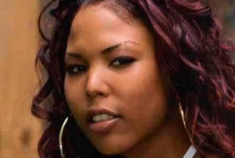 Alicia Simmons is a black transwoman with hoop earrings and curly red hair.