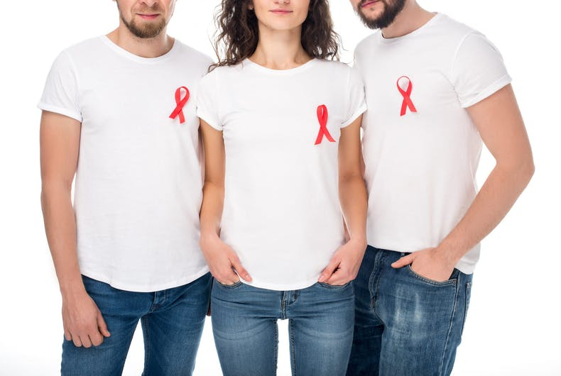 Three people with red ribbons