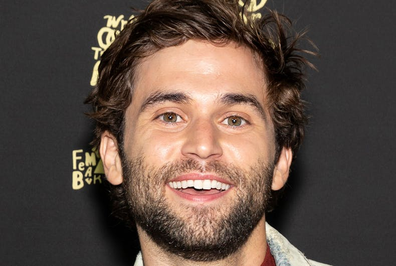 Jake Borelli smiles at a red carpet event