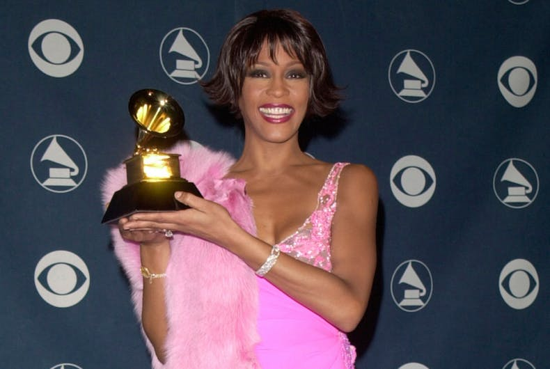 Whitney Houston holds up a Grammy Award. She's wearing a pink dress.