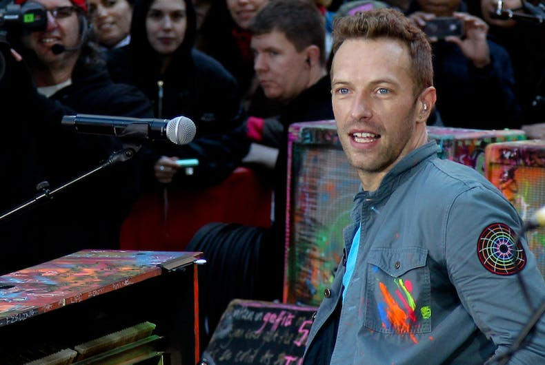 Chris Martin, the leader singer of Coldplay, plays a rainbow colored piano