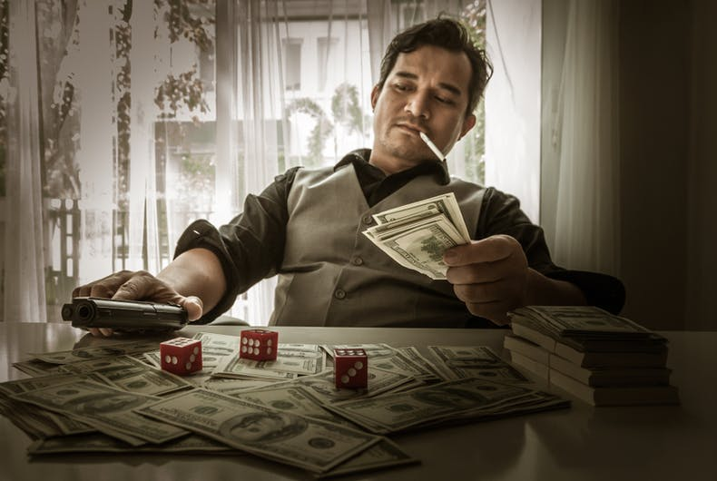 A mafia member counts his money while smoking and drinking and holding a gun.