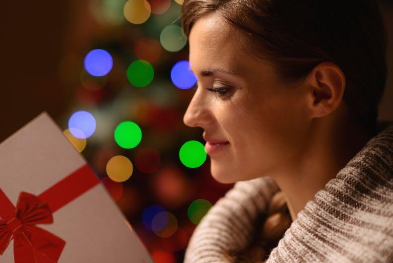 Young woman reading Christmas postcard