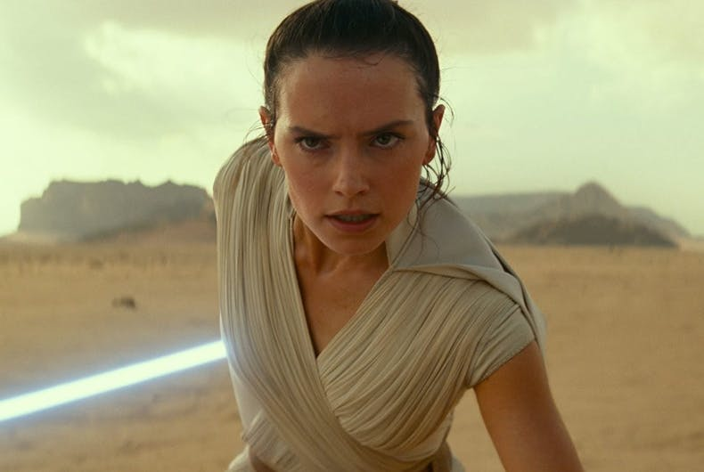 A woman running in a desert with a light saber