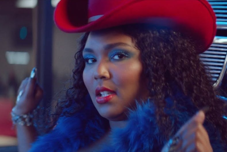 Lizzo wears a boa and a cowboy hat in her video for