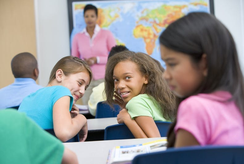 An elementary school girl ashamed in class as other girls laugh at her, with a teacher in the background