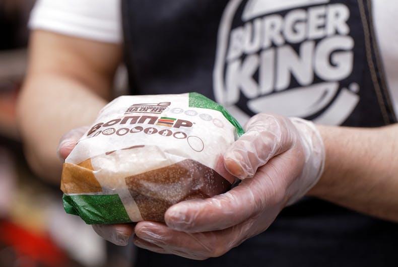Burger King worker holding a hamburger