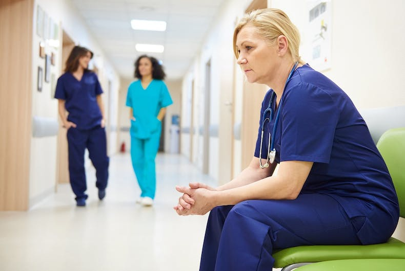A doctor looks forlorn while two other medical staff talk behind her. Maybe she was the victim of anti-LGBTQ patient harassment?