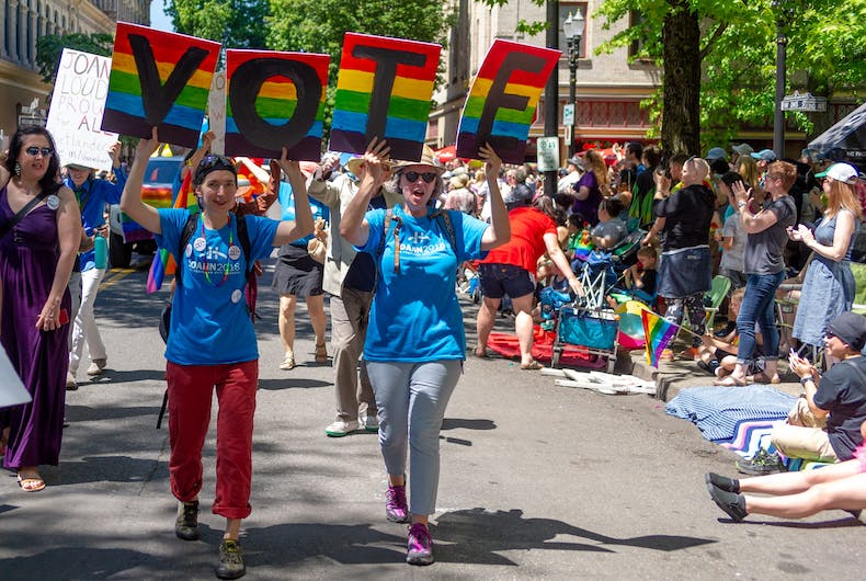 Two women urge LGBTQ people to vote in the next election during the 2018 pride parade in Portland, Oregon.