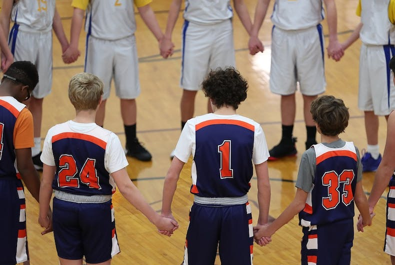 Teens hold hands in prayer before a basketball game