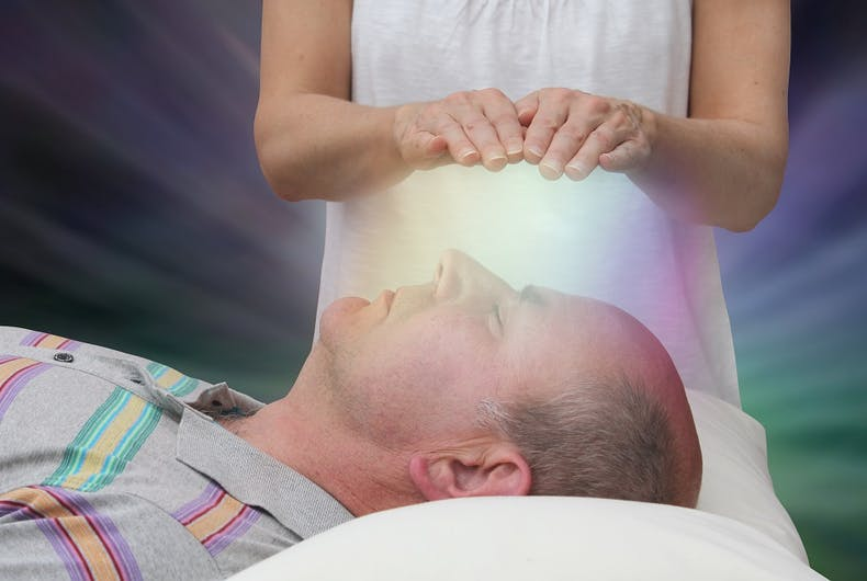 A man being faith-healed by a woman's hands. Faith healing is represented by a white light. It's a stock image.