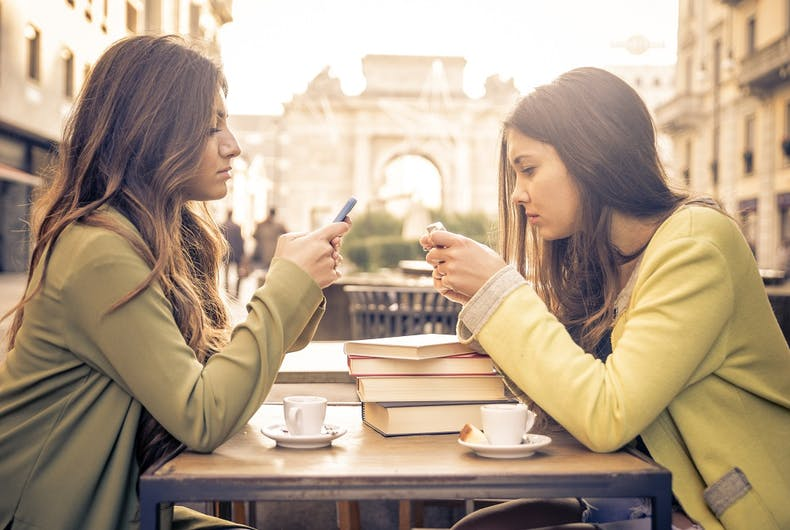 Two women at a table together, looking at their phones instead of talking